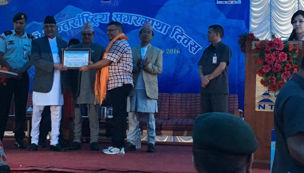 Prime Minister KP Sharma Oli honouring Damber Parajuli, President of Expedition Operator Association of Nepal, for coordinating rope fixing task on Mt Everest, on the occasion of International Mt Everest Day, in Kathmandu, on Sunday, May 29, 2016. Photo: THT