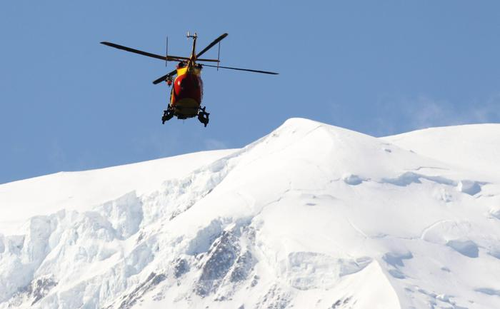epa03304459 A rescue helicopter patrols the air, as part of rescue operations following an avalanche on Mont Maudit mountain, near Chamonix in the French Alps, in France, 12 July 2012. At least six climbers have been killed and eight injured in an avalanche near the Chamonix ski resort, emergency services said.  EPA/GREGORY YETCHMENIZA/LE DAUPHINE FRANCE OUT