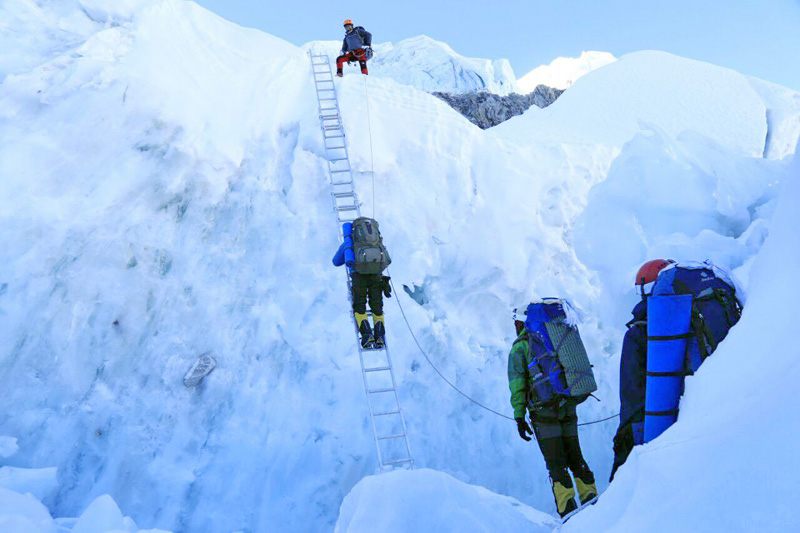 Climber tries to walk past the ladder while ascending to Mt Everest, on Monday, May 9, 2016.