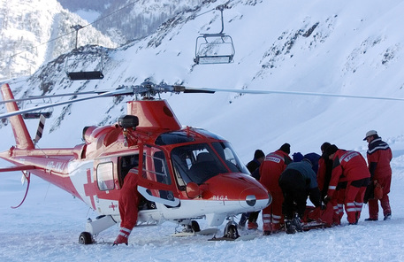 DAV105 - 20000221 - DAVOS, SWITZERLAND : Rescue workers carry a recovered skier to the helicopter, after several skiers and snowboarders were buried alive by an avalanche which went down in the skiing area 'Parsenn' near Davos, Switzerland, Monday, February 21, 2000.  EPA PHOTO KEYSTONE/ANDY METTLER/am-cl