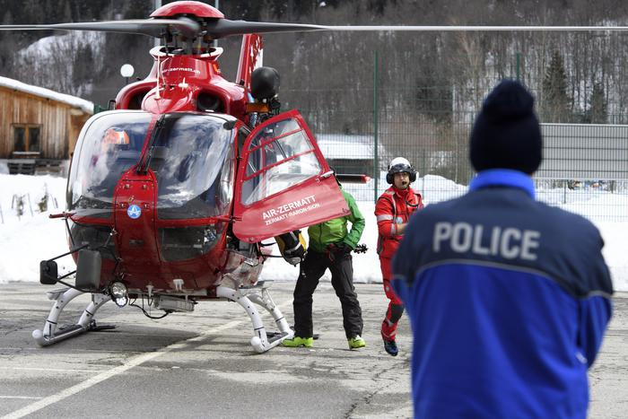 epa06640208 A police officer looks at an Air Zermatt helicopter landing after searching in the area of the avalanche site where five hikers were 'carried away' on 31 March by an avalanche in Obers Taelli over the Fiescheralp, in Fiesch, Switzerland, 01 April 2018. An avalanche reportedly 'carried away' five people on 31 March in Fiesch in the Swiss Upper Valais region. Police said on 01 April that three persons were killed and two others were injured. EPA/JEAN-CHRISTOPHE BOTT