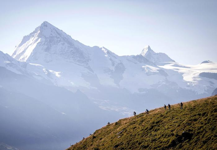 epa04893019 Athletes in action in front of the mountain 'Dent Blanche' (L) and the Matterhorn (R) in val D'Herens, during the Swiss Mountain Bike Marathon 'Grand Raid' from Verbier to Grimentz, Switzerland, 22 August 2015. EPA/OLIVIER MAIRE